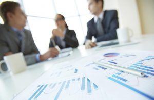 Three business person, out of focus, at a conference table in front of statistical charts