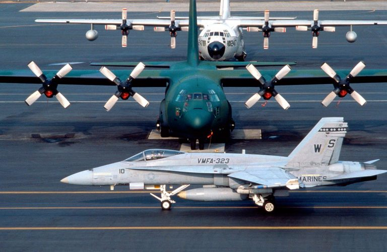 A military jet aircraft and two military cargo airplanes on the tarmac