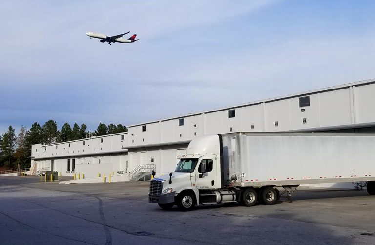 Exterior of Aventure's new warehouse loading dock and truck; airplane taking off in background