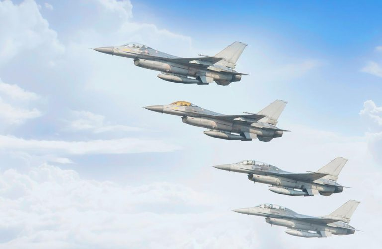 Four F-16 fighter jets flying in close formation in front of a blue sky