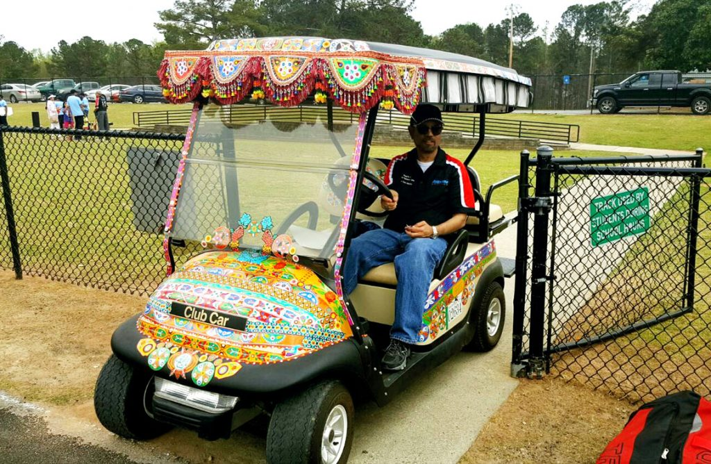 Aventure Aviation President Zaheer Faruqi drives a golf cart to transport cricket spectators