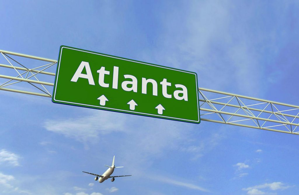 Atlanta highway sign, with airplane in the sky landing