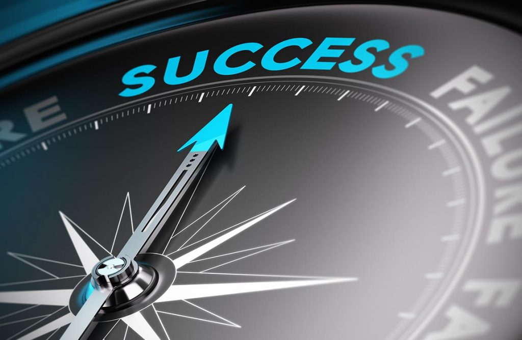 """Close up of a compass pointing to the word """"success"""" at the top of the compass."""