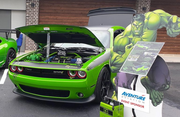A green Dodge Challenger TA next to a cardboard cutout of the Hulk