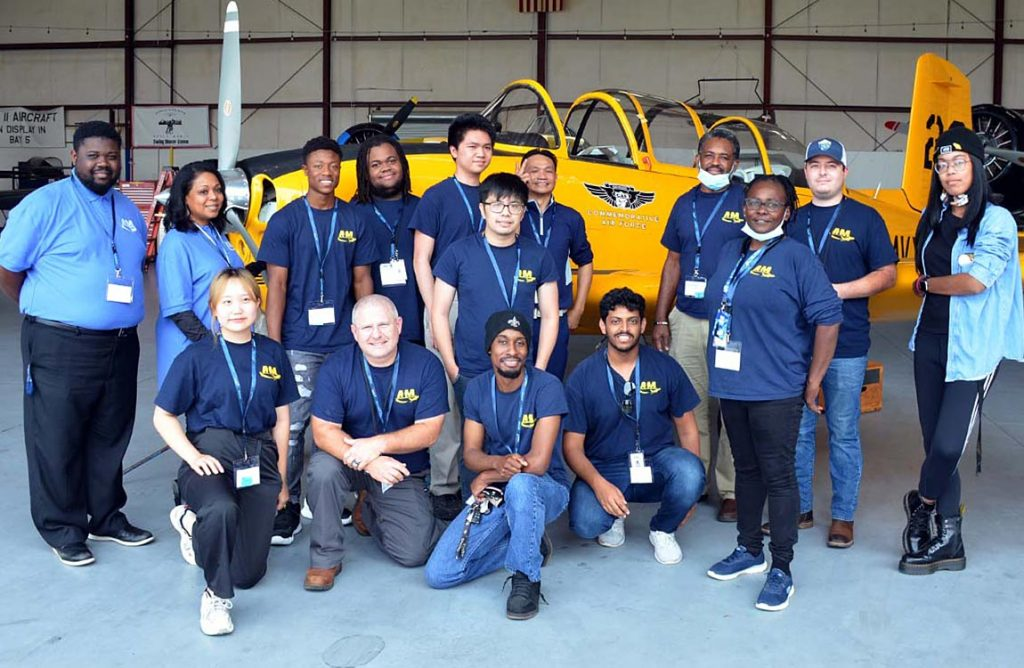 15 aviation students and staff pose in front of a vintage yellow fighter plane at the Commemorative Air Force Dixie Wings Warbird museum