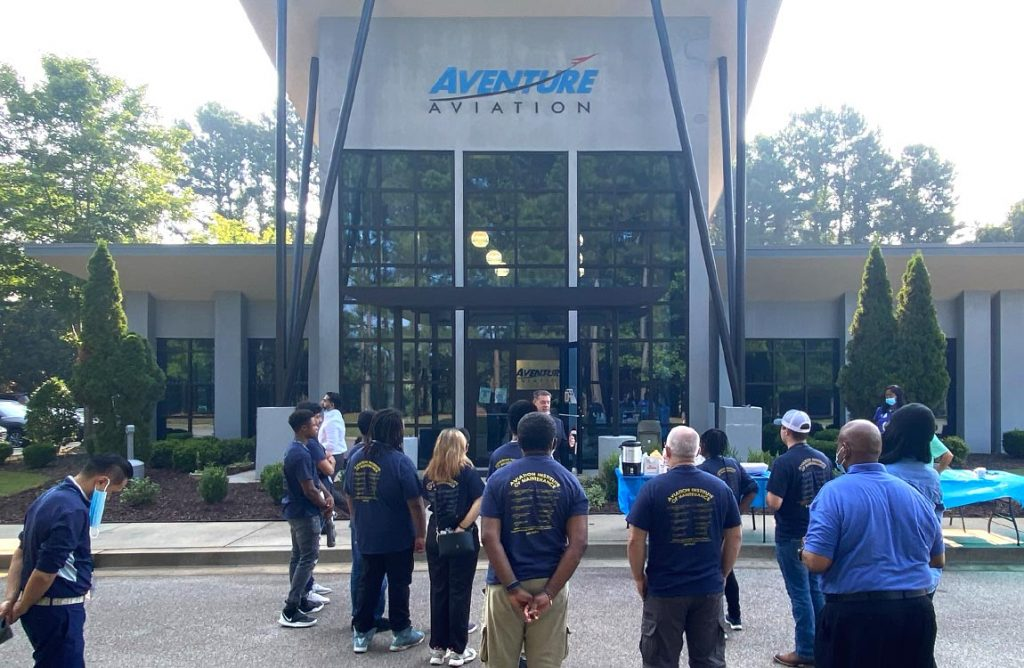 A man addresses about 11 people in front of the Aventure Aviation building