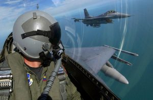 An F-16 fighter pilot in flight watches his wingman from his cockpit