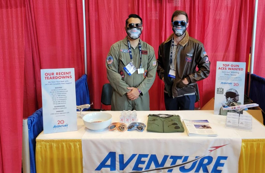 Two men dressed in jet fighter uniforms in front of exhibition booth with Aventure Aviation logo