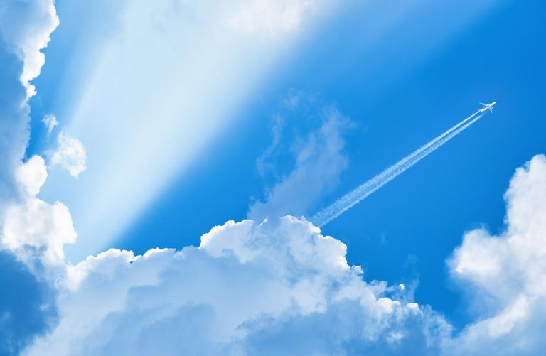Airplane with contrails in the distance with a bright blue sky and huge clouds