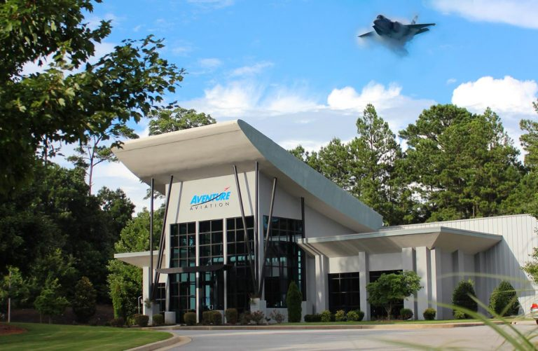 Aventure Aviation's headquarters, with an F-35 fighter jet apearing above it over a blue sky.