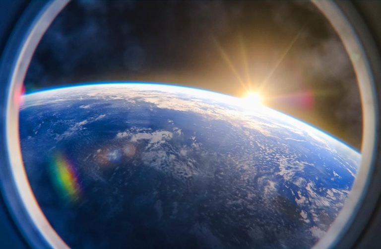 View of a surise over Earth in space from the window of a space ship
